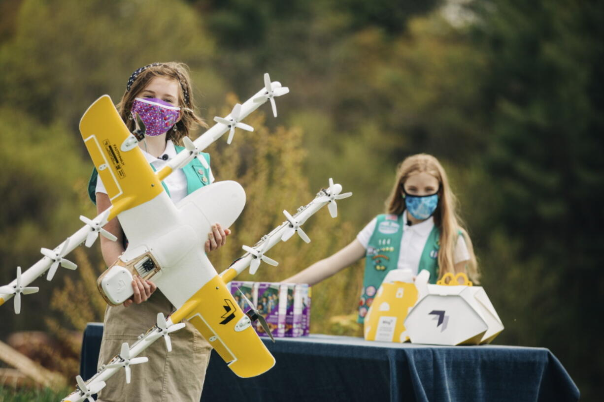 Girl Scouts Alice, right, and Gracie pose April 14 with a Wing delivery drone in Christiansburg, Va. The company is testing drone delivery of Girl Scout cookies in the area.