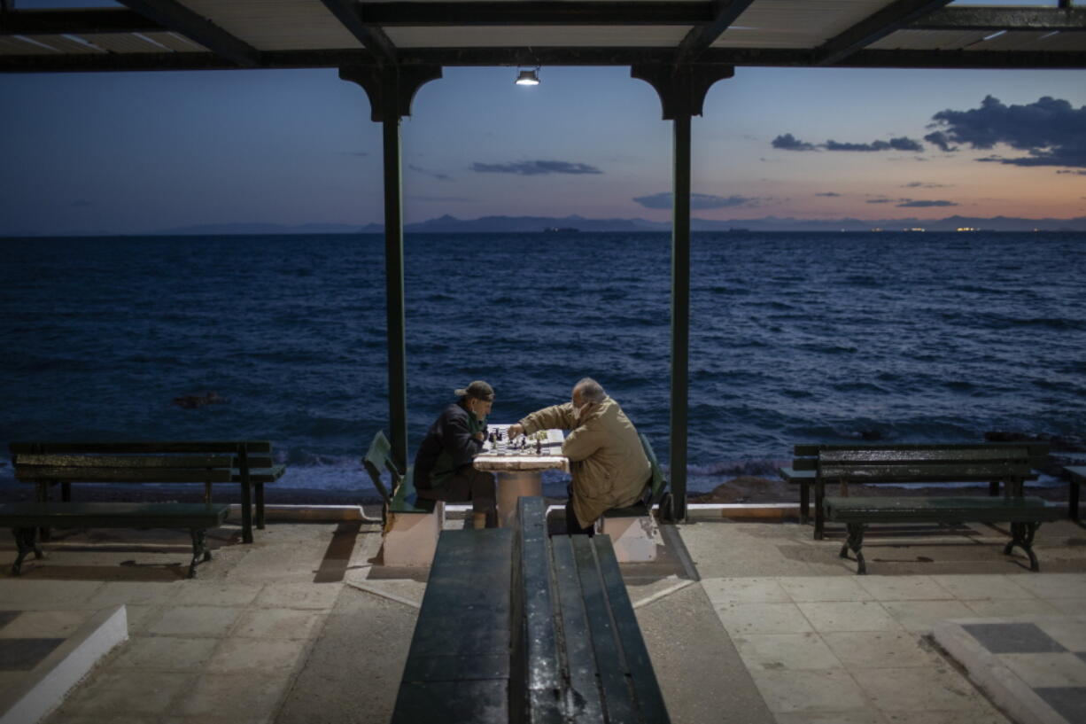 Two men wearing protective face masks play chess in Alimos, a seaside suburb of Athens, on Tuesday, April 20, 2021.
