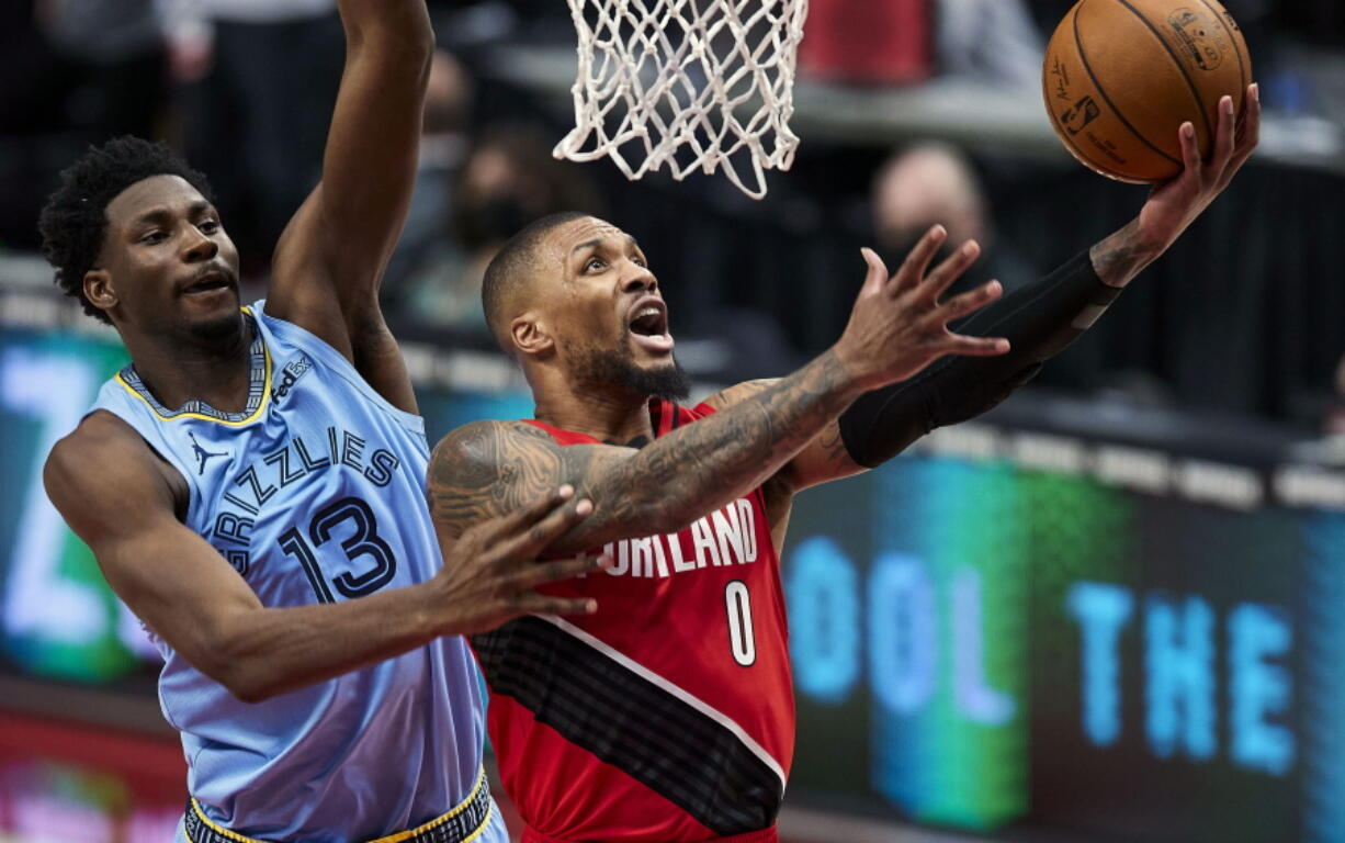 Portland Trail Blazers guard Damian Lillard (0) shoots over Memphis Grizzlies forward Jaren Jackson Jr. (13) during the first half of an NBA basketball game in Portland, Ore., Friday, April 23, 2021.
