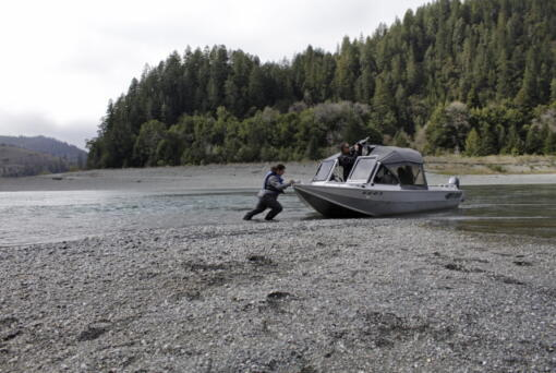 FILE - In this March 5, 2020, file photo, Hunter Maltz, a fish technician for the Yurok tribe, pushes a jet boat into the low water of the Klamath River at the confluence of the Klamath River and Blue Creek as Keith Parker, as a Yurok tribal fisheries biologist, watches near Klamath, Calif., in Humboldt County. One of the worst droughts in memory in the massive agricultural region straddling the California-Oregon border could mean steep cuts to irrigation water for hundreds of farmers this summer to sustain endangered fish species critical to local tribes. The U.S. Bureau of Reclamation, which oversees water allocations in the federally owned Klamath Project, is expected to announce this week how the season's water will be divvied up after delaying the decision a month.