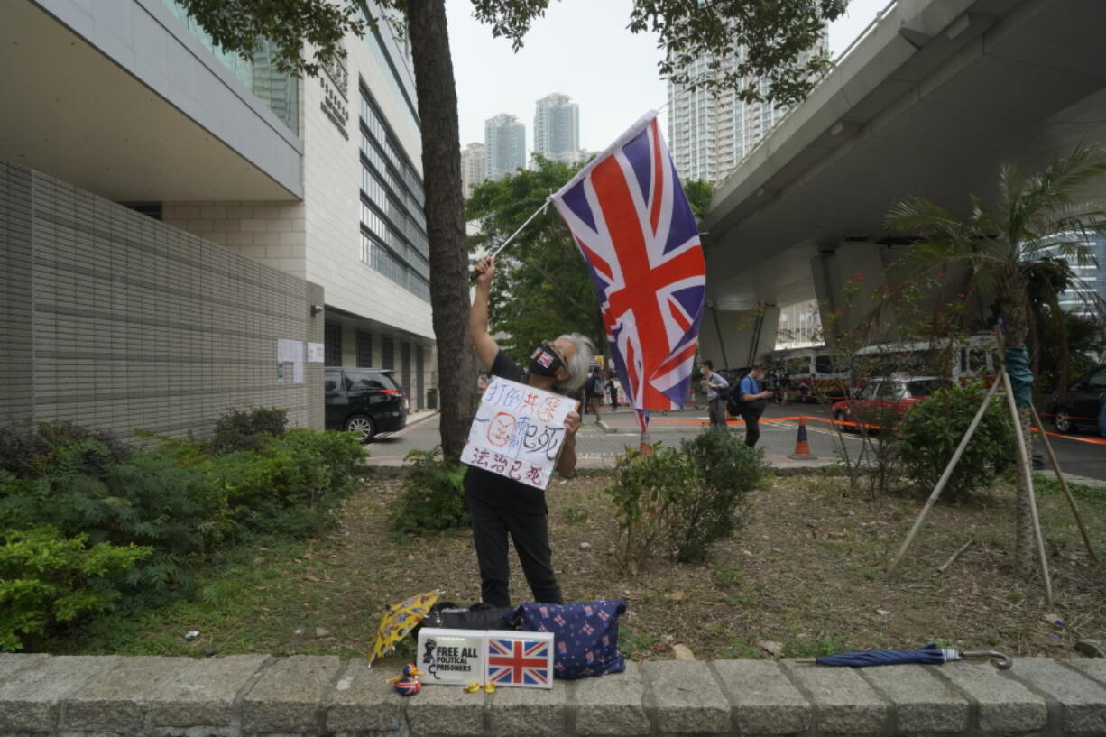 A pro-democracy supporter waves a British flag outside a court in Hong Kong Friday, April 16, 2021.