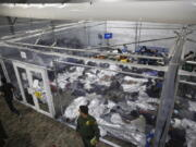 FILE - In this March 30, 2021, file photo, young minors lie inside a pod at the Donna Department of Homeland Security holding facility, the main detention center for unaccompanied children in the Rio Grande Valley run by U.S. Customs and Border Protection (CBP), in Donna, Texas. U.S. authorities say they picked up nearly 19,000 children traveling alone across the Mexican border in March. It's the largest monthly number ever recorded and a major test for President Joe Biden as he reverses many of his predecessor's hardline immigration tactics.