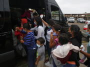 CORRECTS CITY TO MISSION FROM MCALLEN -  Migrants board a van at Our Lady of Guadalupe Catholic Church in Mission, Texas, on Palm Sunday, March 28, 2021. U.S. authorities are releasing migrant families at the border without notices to appear in immigration court and sometimes, without any paperwork at all.