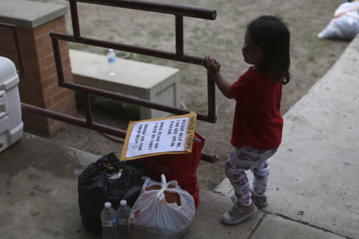A chid stands next to her family's belongings as they wait for transportation at Our Lady of Guadalupe Catholic Church in McAllen, Texas, on Palm Sunday, March 28, 2021. U.S. authorities are releasing migrant families at the border without notices to appear in immigration court, and sometimes without any paperwork at all.