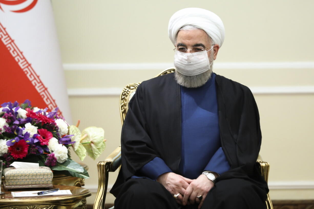 In this photo released by Russian Foreign Ministry Press Service, Iranian President Hassan Rouhani, wearing a face mask to curb the spread of COVD-19, listens to Russian Foreign Minister Sergey Lavrov during their talks in Tehran, Iran, Tuesday, April 13, 2021.