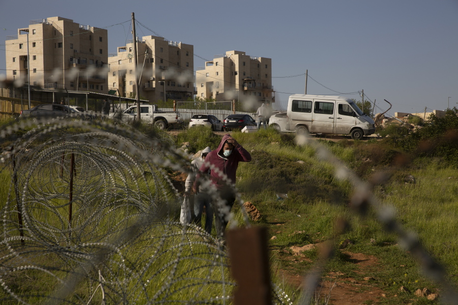Palestinian laborers head home after their work day on construction projects in the West Bank Jewish settlement of Efrat, Tuesday, March 16, 2021. Israel went on an aggressive settlement spree during the Trump era, according to an AP investigation, pushing deeper into the occupied West Bank than ever before and putting the Biden administration into a bind as it seeks to revive Mideast peace efforts.