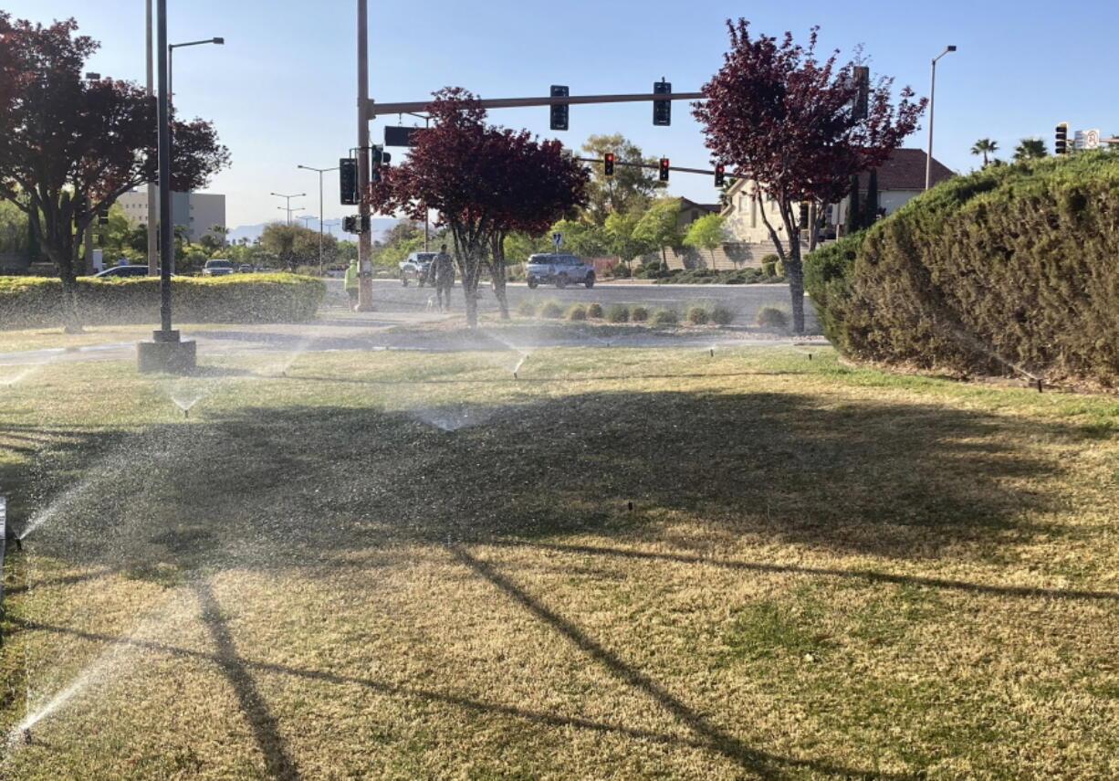 Sprinklers water grass near a street corner Friday, April 9, 2021, in the Summerlin neighborhood of northwest Las Vegas. A desert city built on a reputation for excess wants to become a model for restraint with a first-in-the-nation policy limiting water use by banning grass that nobody walks on.