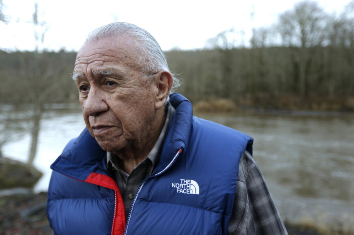 FILE - In this Jan. 13, 2014, file photo, Billy Frank Jr. poses for a photo near Frank's Landing on the Nisqually River in Nisqually, Wash. Gov. Jay Inslee on Wednesday, April 14, 2021, signed a measure that starts the process of honoring the late Frank, a Nisqually tribal member who championed treaty rights and protecting the environment, with a statue at the U.S. Capitol. (AP Photo/Ted S.