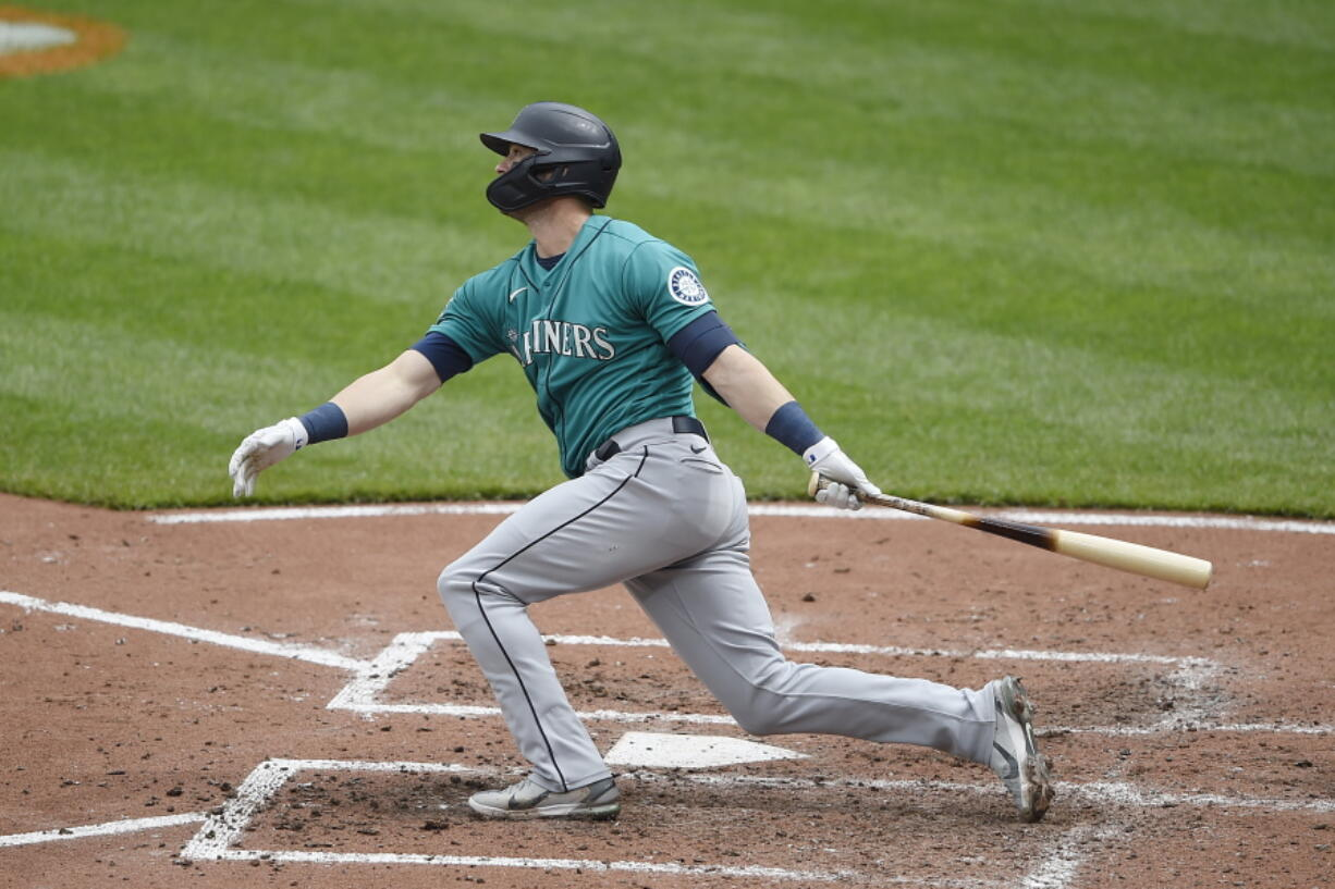 Seattle Mariners' Mitch Haniger follows through on a two run home run against the Baltimore Orioles in the fifth inning of the first game of a baseball doubleheader, Thursday, April 15, 2021, in Baltimore.