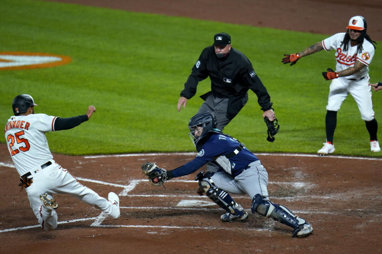 Baltimore Orioles' Anthony Santander (25) slides into home as Seattle Mariners catcher Luis Torrens tries to apply the tag during the third inning of the second game of a baseball doubleheader, Tuesday, April 13, 2021, in Baltimore. The ball kicked away from from Torrens and Santander was ruled safe. On the play, Santander, Freddy Galvis and DJ Stewart scored on a bases loaded double by Maikel Franco.