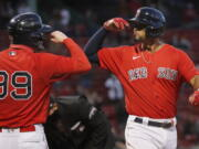 Boston Red Sox's Xander Bogaerts celebrates his two-run home run that also drove in Alex Verdugo (99) during the first inning of a baseball game against the Seattle Mariners, Friday, April 23, 2021, in Boston.