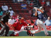 Seattle Mariners' Kyle Seager follows through on his two-run triple in front of Boston Red Sox's Kevin Plawecki during the second inning of a baseball game Saturday, April 24, 2021, in Boston.
