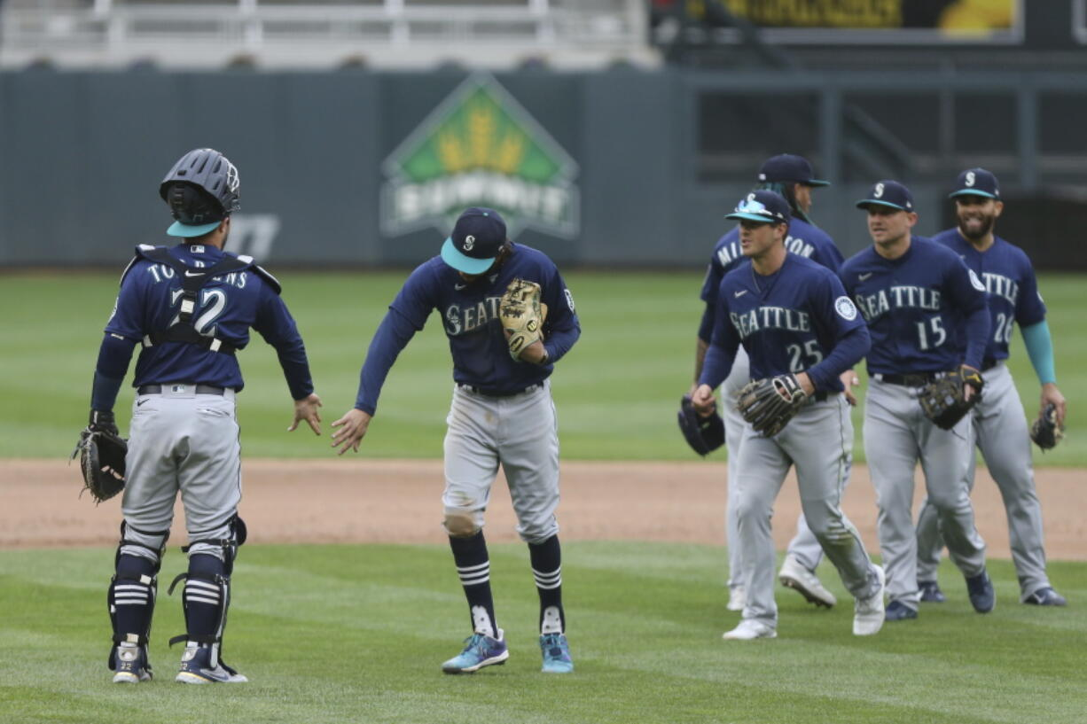 Seattle Mariners' J.P. Crawford (3) slaps hands with catcher Luis Torrens (22) after their 4-3 win against the Minnesota Twins after the 10th inning of a baseball game, Saturday, April 10, 2021, in Minneapolis.