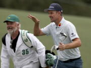 Justin Rose and his caddie David Clark react to his second shot on the eighteenth hole during the first round of the Masters golf tournament at Augusta National Golf Club, Thursday, April 8, 2021, in Augusta, Ga.