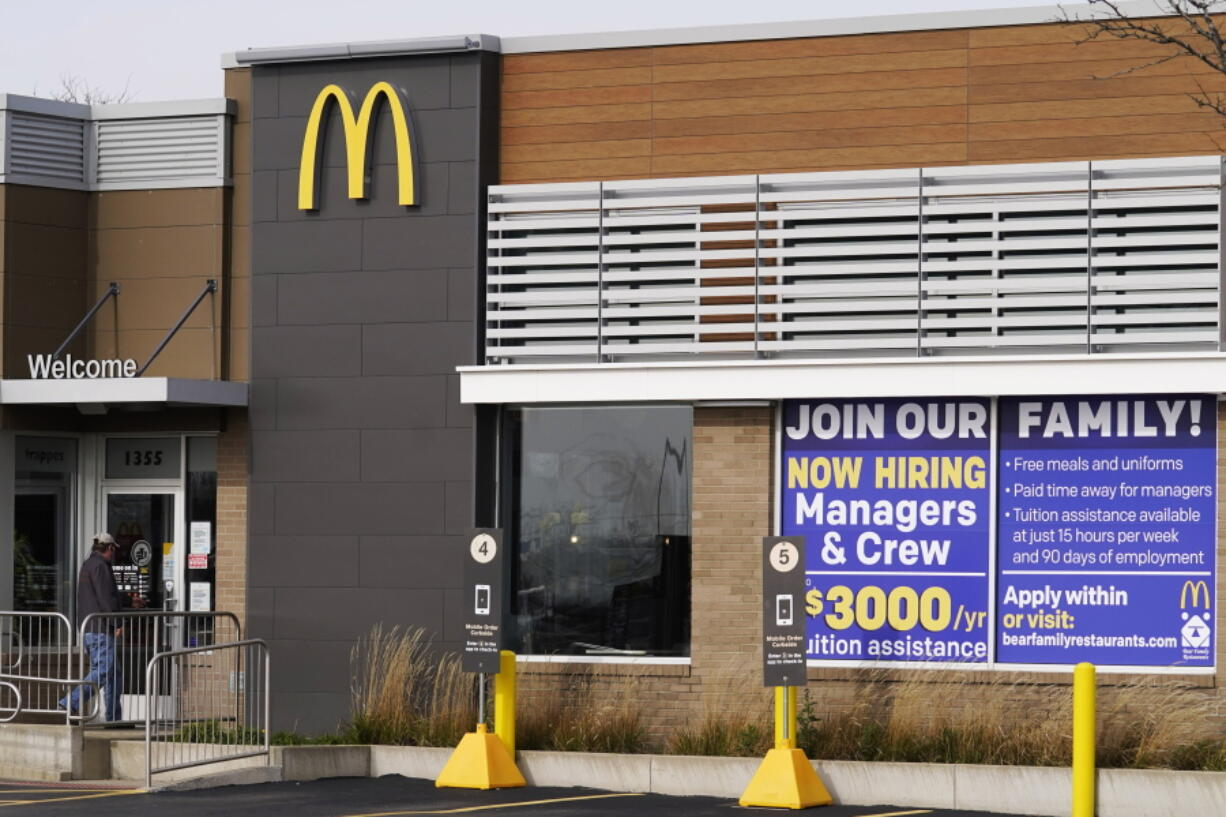 FILE - In this Nov. 19, 2020, file photo, a hiring sign is displayed outside of McDonald's in Buffalo Grove, Ill. On Wednesday, April 14, 2021, McDonald's said the company will mandate worker training to combat harassment, discrimination and violence in its restaurants worldwide starting in 2022.  (AP Photo/Nam Y.