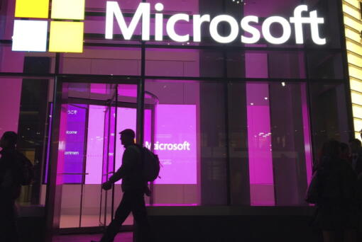 FILE - In this Nov. 10, 2016, file photo, people walk near a Microsoft office in New York. Microsoft, on an accelerated growth push, is buying speech recognition company Nuance in a deal worth $19.7 billion including debt.  (AP Photo/Swayne B.
