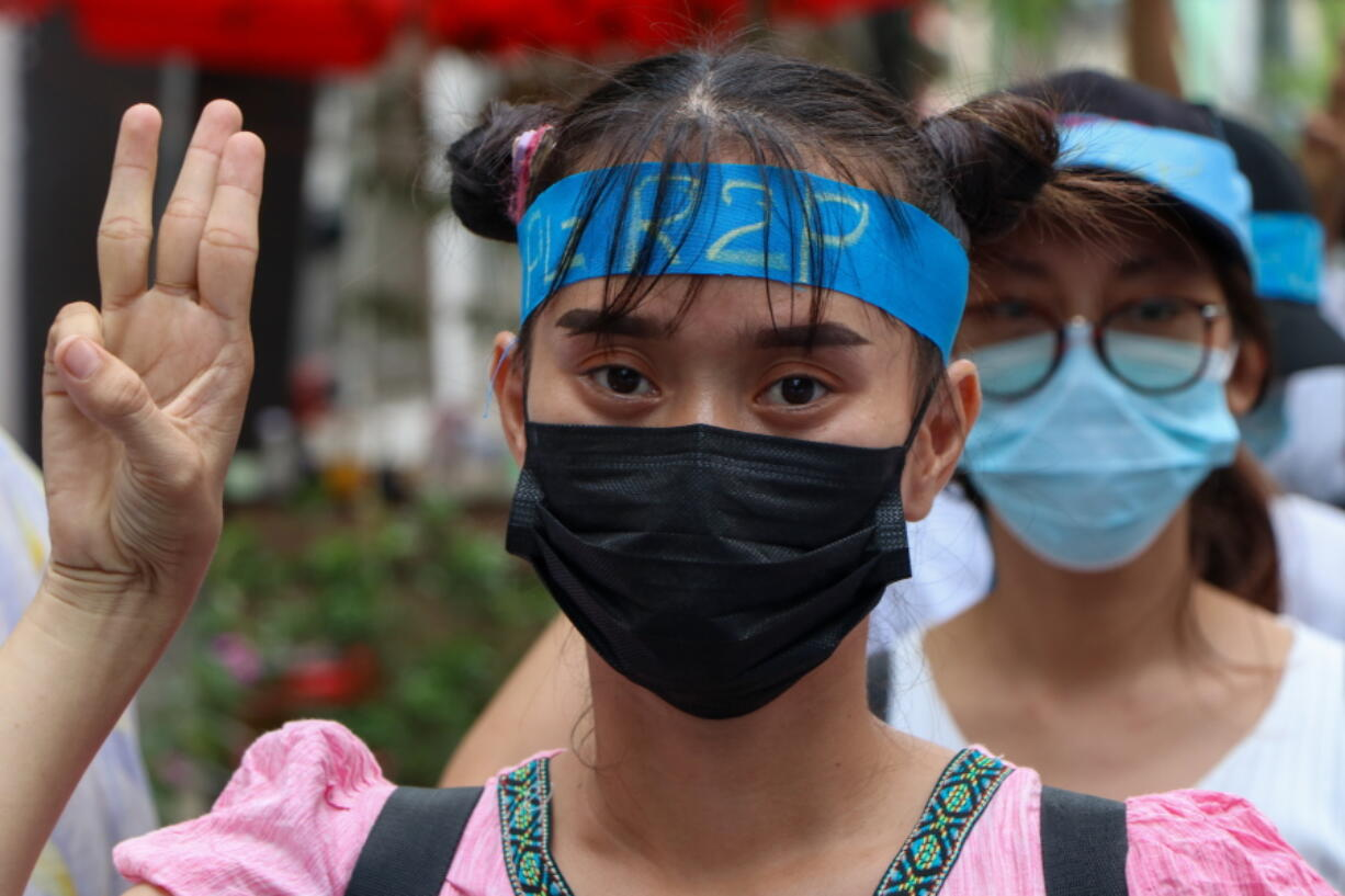 An anti-coup protester flashes the three-fingered salute while wearing a headband that reads R2P, which means Responsibility to Protect, during a gathering in Ahlone township in Yangon, Myanmar Monday, April 12, 2021. The protesters have called for foreign intervention to aid them under the doctrine of Responsibility to Protect, or R2P, devised to deal with matters such as genocide, war crimes, ethnic cleansing and crimes against humanity.