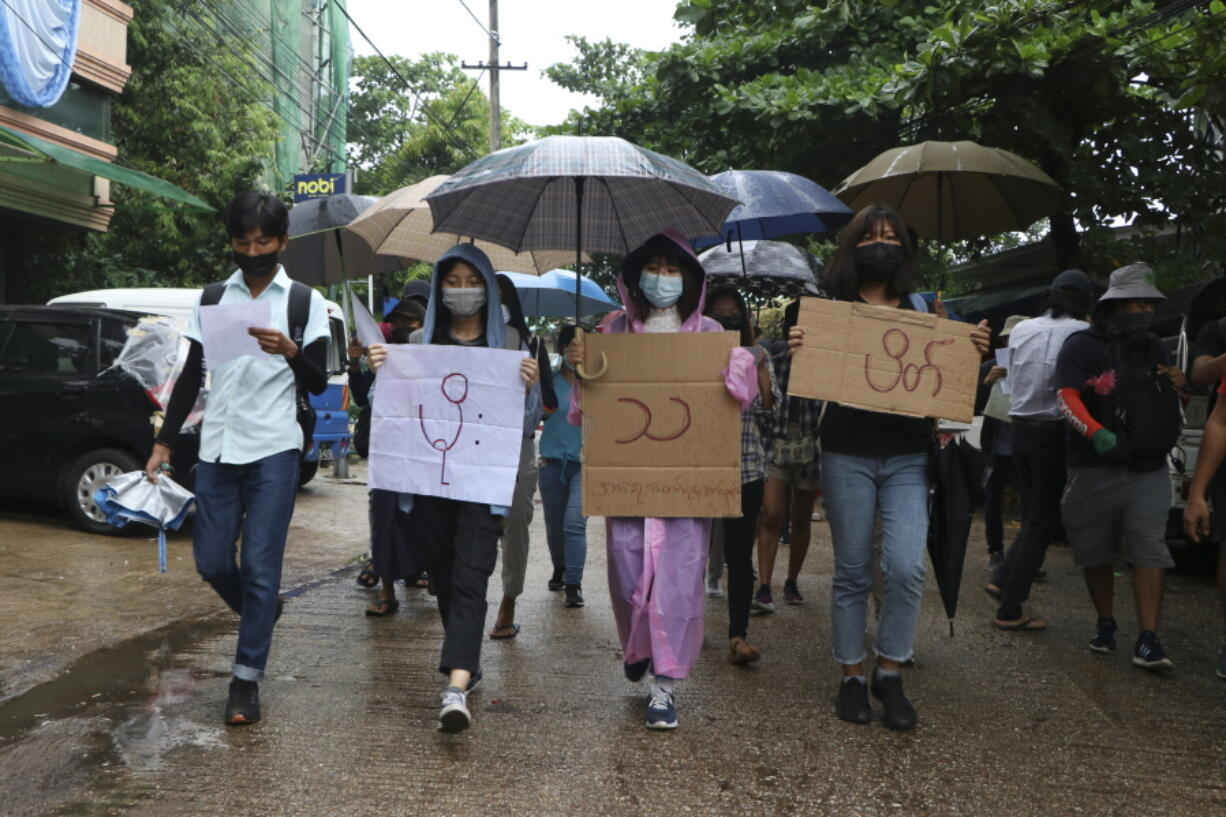 "Anti-coup protesters hold slogans which read ""Rain Strike"" as they use their umbrellas during a drizzle while participating in a demonstration in Yangon, Myanmar on Tuesday April 6, 2021. Threats of lethal violence and arrests of protesters have failed to suppress daily demonstrations across Myanmar demanding the military step down and reinstate the democratically elected government."