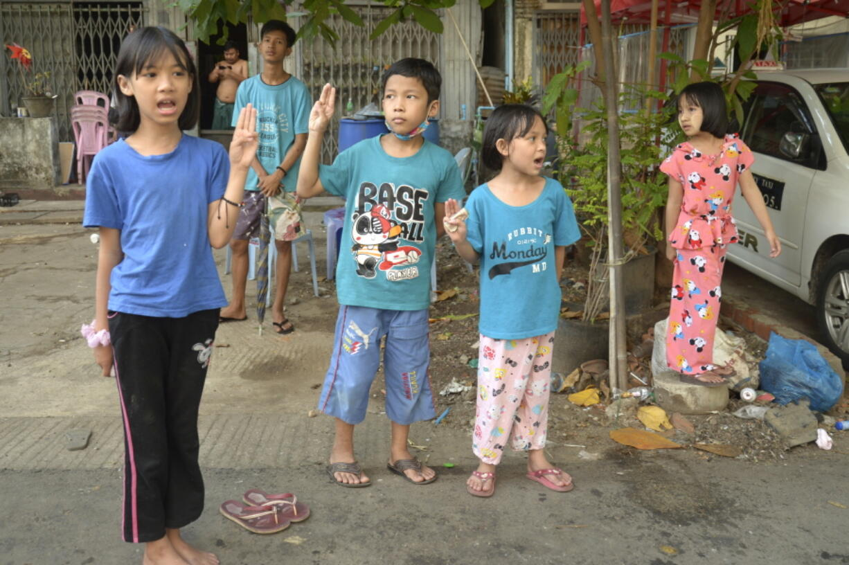 Children flash the three-fingered symbol of resistance as they join an anti-coup protest in Yangon, Myanmar, Saturday, April 10, 2021.