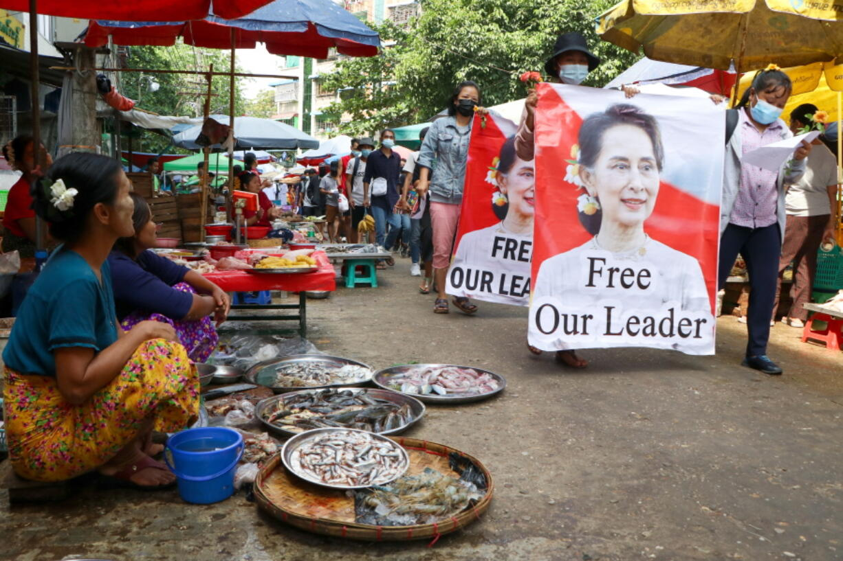 Anti-coup protesters walk through a market with images of ousted Myanmar leader Aung San Suu Kyi at Kamayut township in Yangon, Myanmar Thursday, April 8, 2021. They walked through the markets and streets of Kamayut township with slogans to show their disaffection for military coup.
