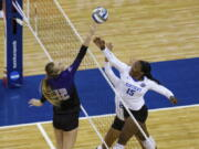 Washington's Marin Grote (12) bumps the ball over Kentucky's Azhani Tealer (15) during the first set of a semifinal in the NCAA women's volleyball championships Thursday, April 22, 2021, in Omaha, Neb.