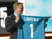NFL Commissioner Roger Goodell holds a Jacksonville Jaguars jersey as he announces that the Jaguars had chosen Clemson quarterback Trevor Lawrence with the first pick in the NFL football draft, Thursday April 29, 2021, in Cleveland.