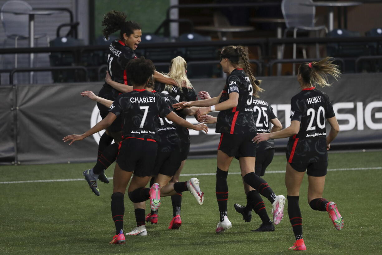 Portland Thorns players celebrate a goal scored by Portland's Rocky Rodriguez (11), left, against Kansas City during an NWSL Challenge Cup soccer match, Friday, April 9, 2021, in Portland, Ore.