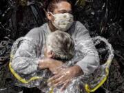 The First Embrace, shows Rosa Luzia Lunardi, 85, embraced by nurse Adriana Silva da Costa Souza, at Viva Bem care home, Sao Paulo, Brazil, on Aug. 5, 2020. The photo won the World Press photo of the year.