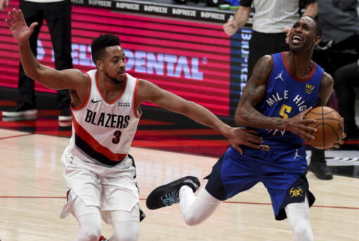 Portland Trail Blazers guard CJ McCollum, left, fouls Denver Nuggets forward Will Barton during the first half of an NBA basketball game in Portland, Ore., Wednesday, April 21, 2021.