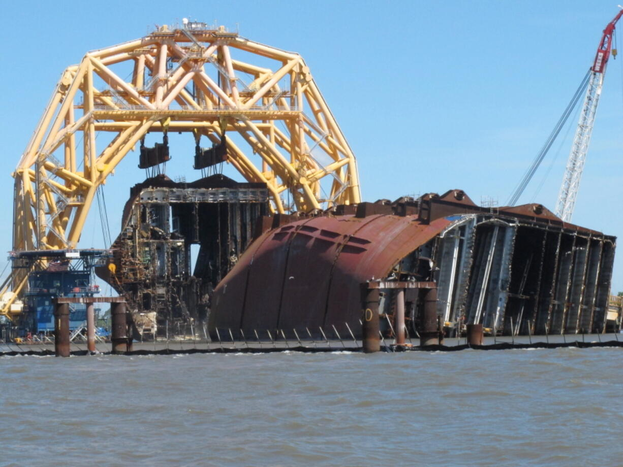 A towering crane pulls the engine room section away from the remains of the capsized cargo ship Golden Ray on Monday, April 26, 2021, offshore of St. Simons Island, Ga. The South Korean vessel capsized with roughly 4,200 vehicles in its cargo decks in September 2019. The engine room section is the fourth giant chunk of the ship to be cut away and removed since demolition began in November 2020.