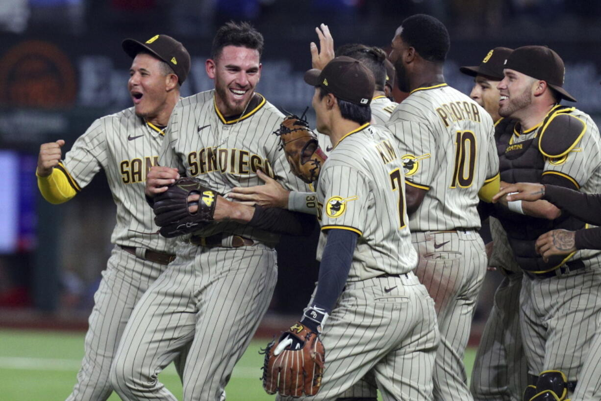 San Diego Padres starting pitcher Joe Musgrove, second from left, is mobbed by teammates after pitching a no-hitter against the Texas Rangers in a baseball game Friday, April 9, 2021, in Arlington, Texas. (AP Photo/Richard W.