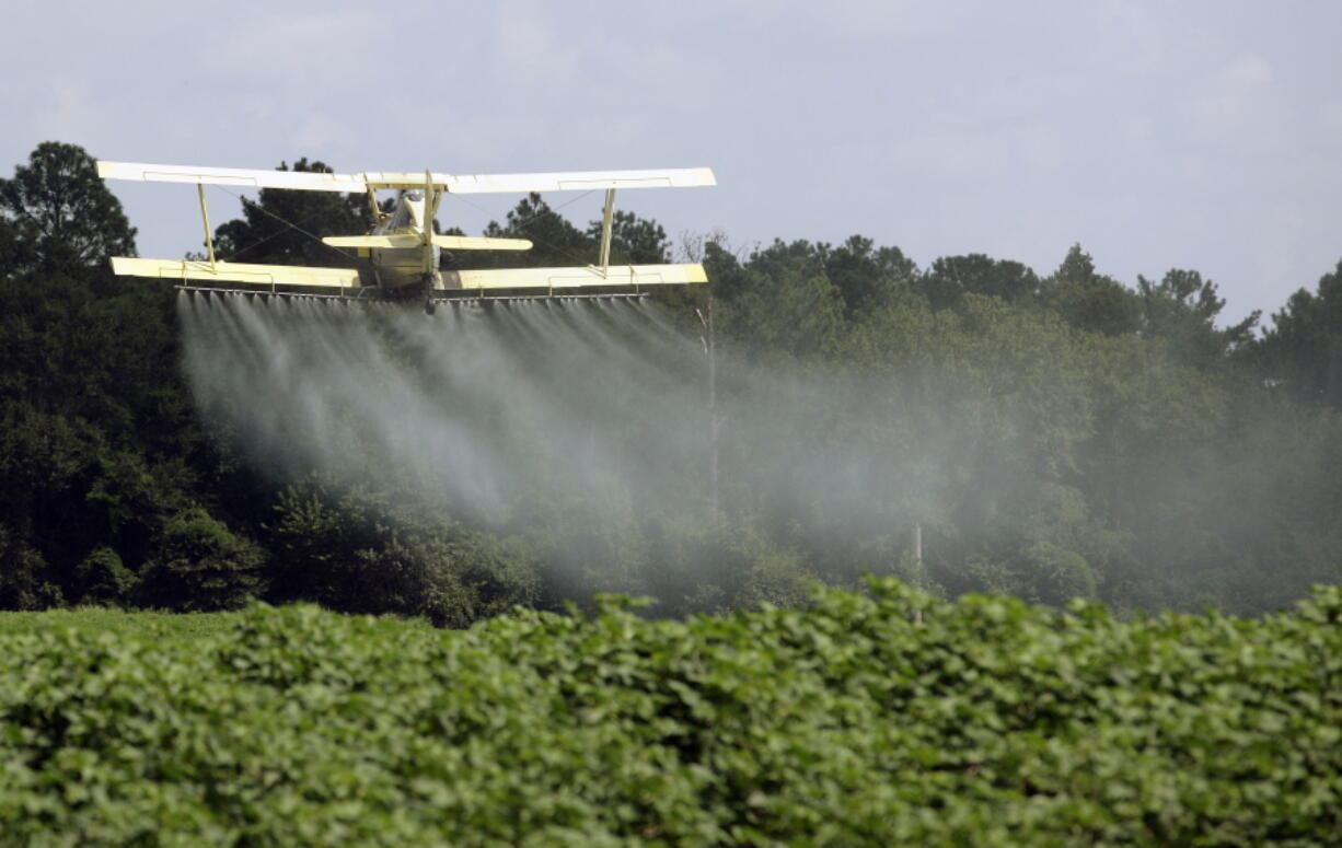 FILE - In this Aug. 4, 2009 file photo, a crop duster sprays a field in Alabama. A study published in the journal Science on Thursday, April 1, 2021 finds that farmers in the U.S. are using smaller amounts of better targeted pesticides, but these are harming pollinators, aquatic insects and some plants far more than decades ago.