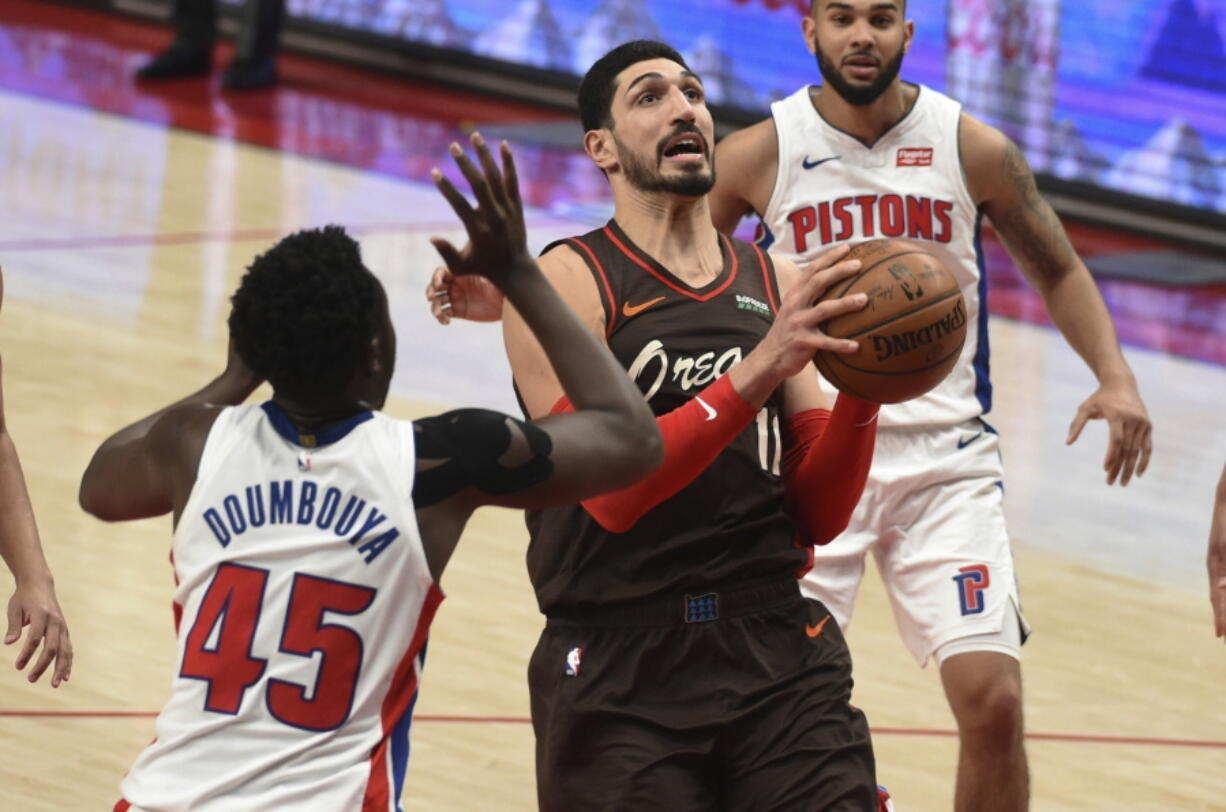 Portland Trail Blazers center Enes Kanter drives to the basket on Detroit Pistons forward Sekou Doumbouya, left, during the second half of an NBA basketball game in Portland, Ore., Saturday, April 10, 2021. The Blazers won 118-103.