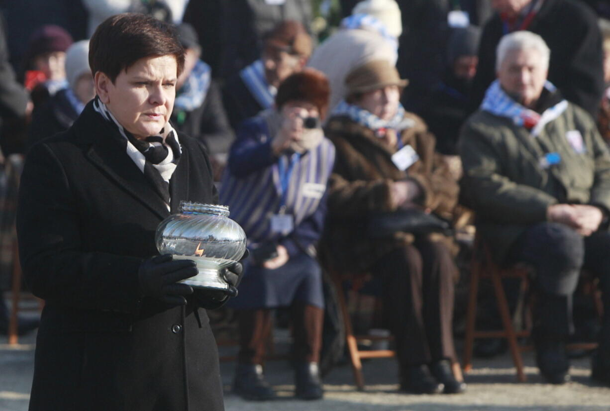FILE - In this Friday, Jan. 27, 2017 file photo, Polish Prime Minister Beata Szydlo lights a candle at the International Monument to the Victims of Fascism, after a ceremony marking the 72nd anniversary of the liberation of the German Nazi death camp Auschwitz-Birkenau, in Oswiecim, Poland. Three of nine members appointed to an advisory council for the Auschwitz-Birkenau museum in Poland have resigned in protest after the government also named Beata Szydlo, a top right-wing ruling party member, to serve on the body it was announced Friday, April 16, 2021. The culture minister appointed Szydlo recently to a four-year term on the Auschwitz-Birkenau State Museum Council, a body made up of Poles who meet once a year to advise the director but which has little real influence.