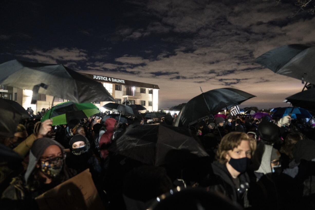 """""""Justice 4 Daunte"""" is projected onto a residence as people take part in a protest near the Brooklyn Center Police Department over Sunday's fatal shooting of Daunte Wright during a traffic stop, Thursday, April 15, 2021, in Brooklyn Center, Minn."""