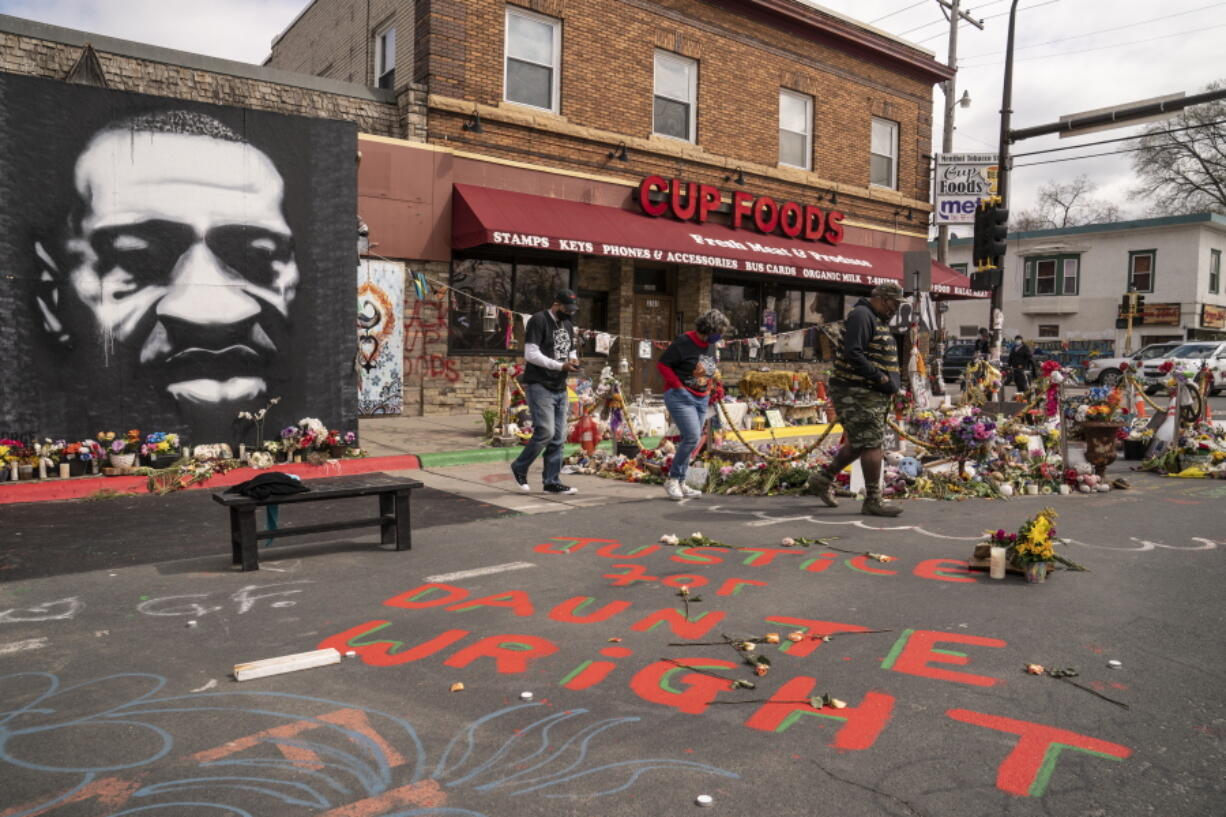 Visitors browse a memorial to George Floyd as a new addition commemorating Daunte Wright is displayed outside Cup Foods, Wednesday, April 14, 2021, in Minneapolis, Minn.