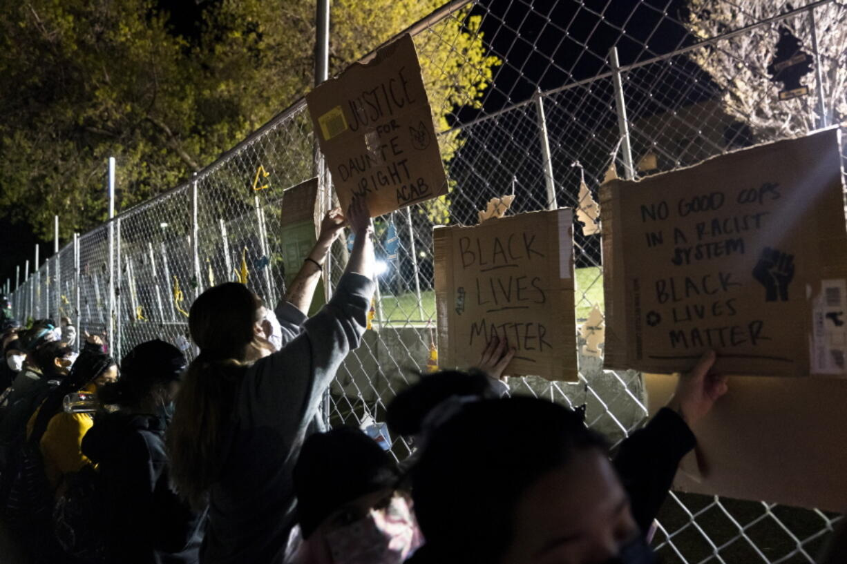 Demonstrators press against a perimeter security fence during a protest over the fatal shooting of Daunte Wright during traffic stop, outside the Brooklyn Center Police Department, Friday, April 16, 2021, in Brooklyn Center, Minn.