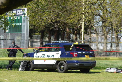 A Portland Police officer stand by following a police involved shooting of a man at Lents Park, Friday, April 16, 2021, in Portland, Ore. Police fatally shot a man in the city park Friday morning after responding to reports of a person with a gun, authorities said.