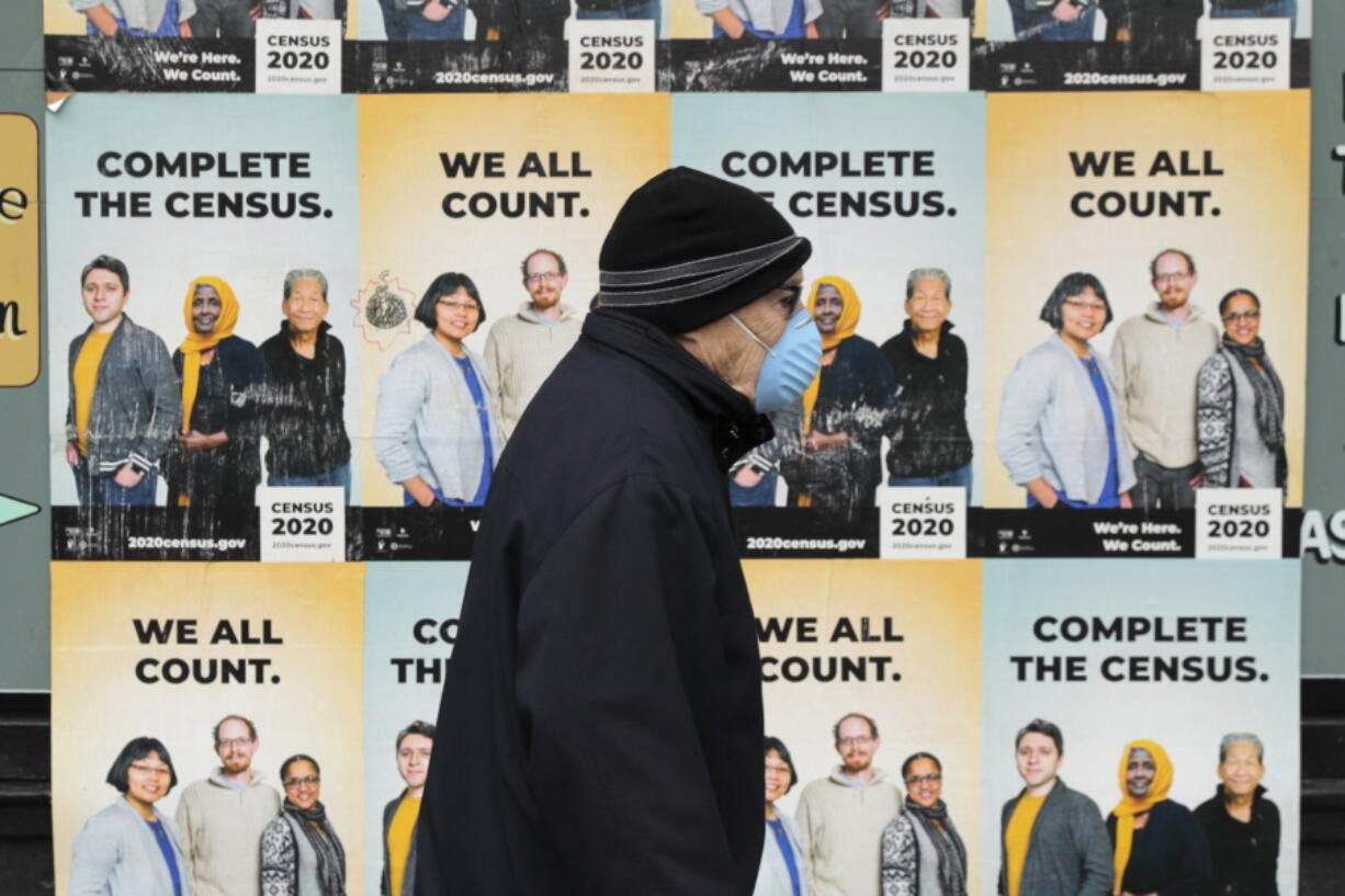 FILE - In this April 1, 2020, file photo, a man wearing a mask walks past posters encouraging participation in the 2020 Census in Seattle's Capitol Hill neighborhood. A delay in census data is scrambling plans in some states to redraw districts for the U.S. House and state legislatures. The Census Bureau has said redistricting data that was supposed to be provided to states by the end of March won't be ready until August or September. (AP Photo/Ted S.