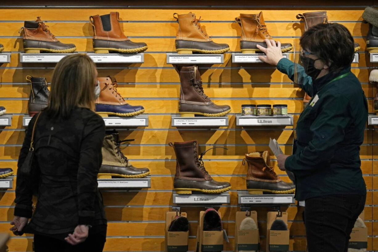 A salesperson helps a customer shopping for boots at the L.L. Bean flagship retail store in Freeport, Maine, on March 18. Newly vaccinated and armed with $1,400 stimulus checks, Americans went on a spending spree last month, buying new clothes and going out to eat again, the Commerce Department said Thursday. (robert f.