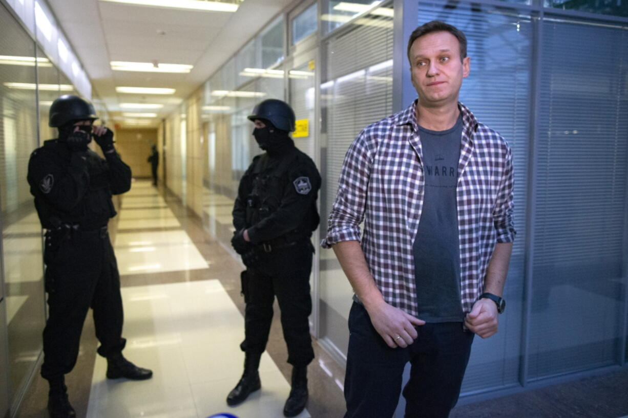 FILE - In this Thursday, Dec. 26, 2019 file, Russian opposition leader Alexei Navalny speaks to the media in front of security officers standing guard at the Foundation for Fighting Corruption office in Moscow, Russia. A court in Moscow has ruled to restrict activities of an organization founded by Russia's imprisoned opposition leader Alexei Navalny, pending a ruling on whether it should be outlawed as an extremist group. The Moscow City Court's decision to restrict activities of Navalny's Foundation for Fighting Corruption came amid a sweeping crackdown on President Vladimir Putin most prominent critic and his allies.