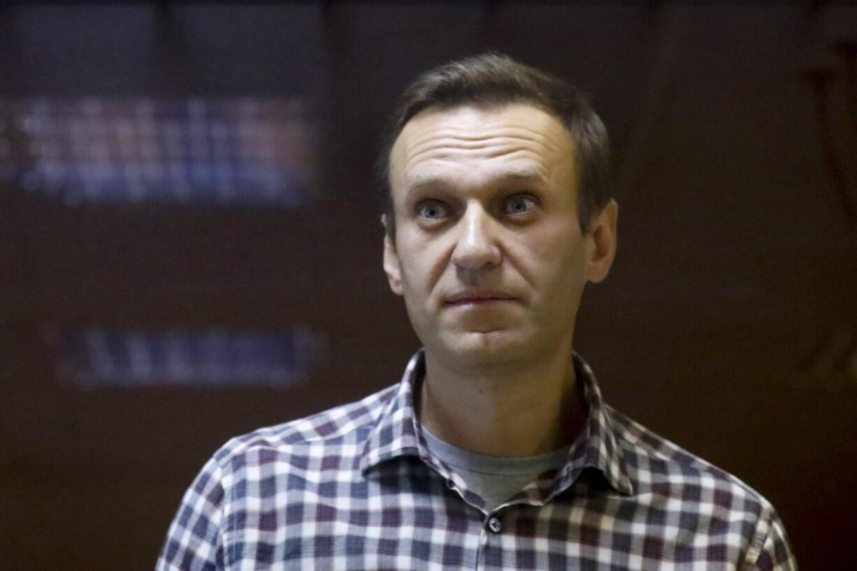 "FILE - In this Saturday, Feb. 20, 2021 file photo, Russian opposition leader Alexei Navalny stands in a cage in the Babuskinsky District Court in Moscow, Russia. Imprisoned Russian opposition leader Alexei Navalny, who has been on hunger strike since March 31, described threats to force-feed him, using ""straitjacket and other pleasures,"" in a message from behind bars Friday, April 16. In an Instagram post, Navalny said an official told him that a blood test indicated his health was deteriorating and threatened to force-feed him if he continues to refuse to eat."