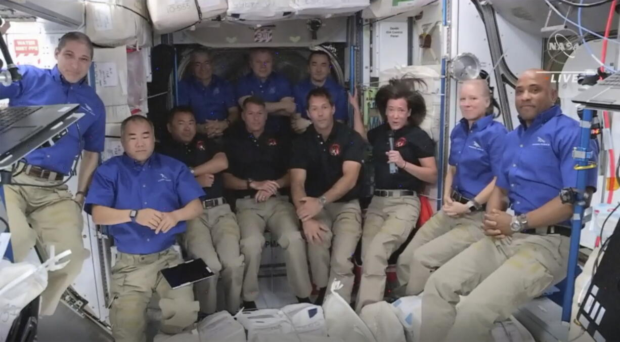 This image provided by NASA, astronauts from SpaceX join the astronauts of the International Space Station for an interview on Saturday, April 24, 2021.  A recycled SpaceX capsule carrying four astronauts has arrived at the International Space Station, a day after launching from Florida. The Dragon capsule docked autonomously with the orbiting outpost on Saturday.
