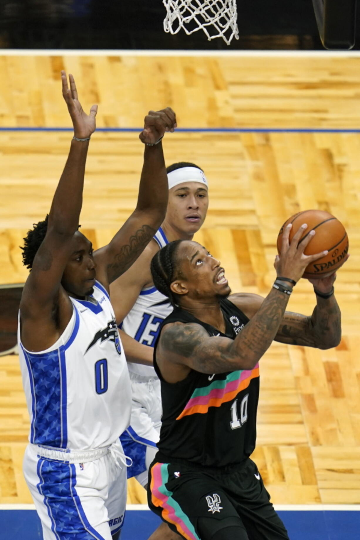 San Antonio Spurs forward DeMar DeRozan, right, looks for a shot against Orlando Magic's Robert Franks (0) and guard R.J. Hampton, back center, during the second half of an NBA basketball game, Monday, April 12, 2021, in Orlando, Fla.