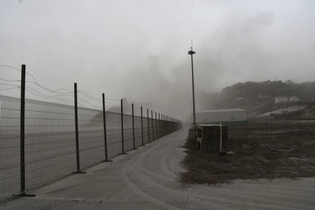 A road is blanketed in volcanic ash at the international airport in Kingstown, on the eastern Caribbean island of St. Vincent, Saturday, April 10, 2021 due to the eruption of La Soufriere volcano.