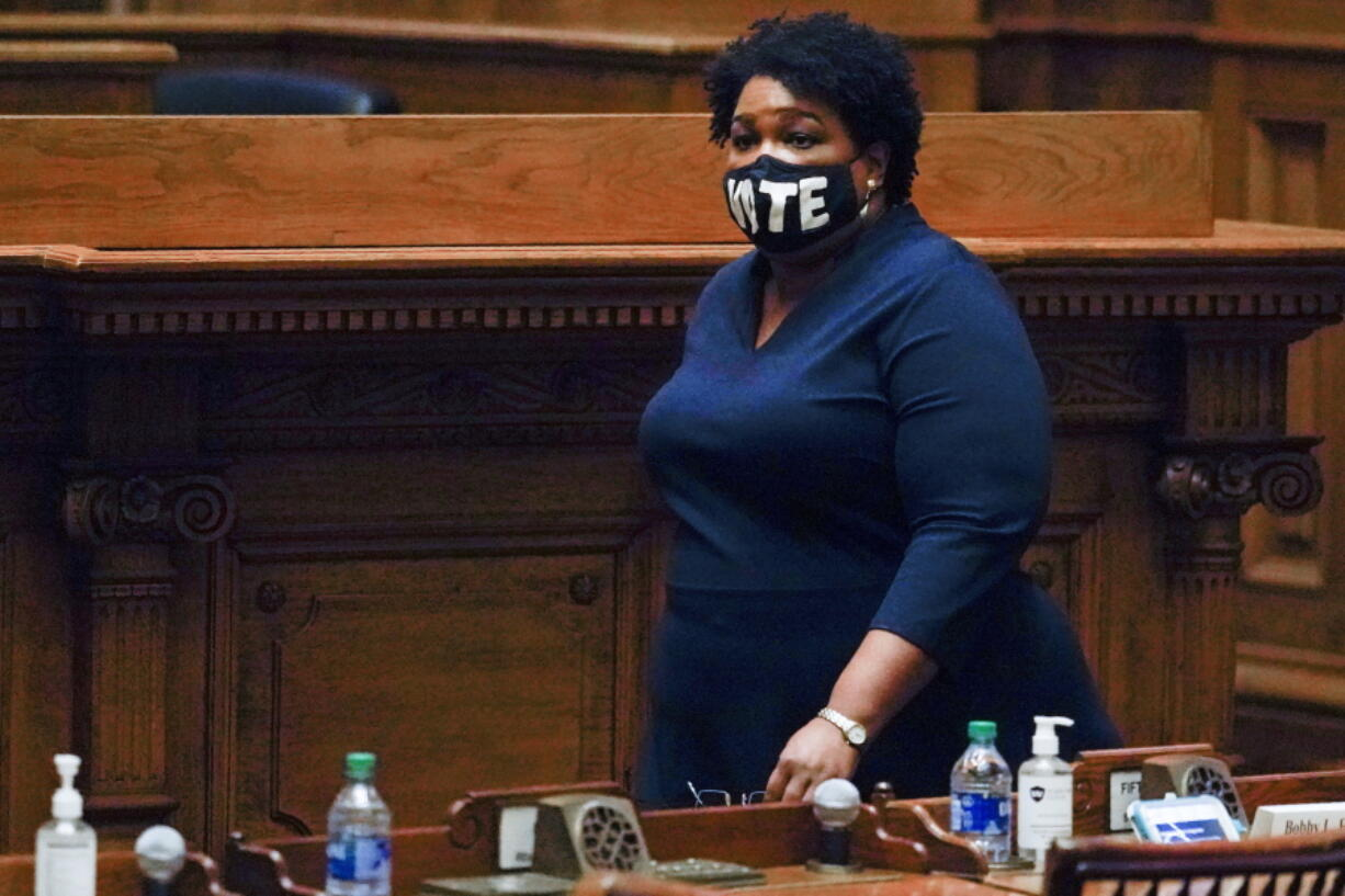 FILE - In this Monday, Dec. 14, 2020, file photo, Democrat Stacey Abrams walks on Senate floor before of members of Georgia's Electoral College cast their votes at the state Capitol in Atlanta. In a new interview with The Associated Press, voting rights advocate Abrams discussed a new state law that tightens some Georgia voting rules after Democrats carried the state in the 2020 elections.