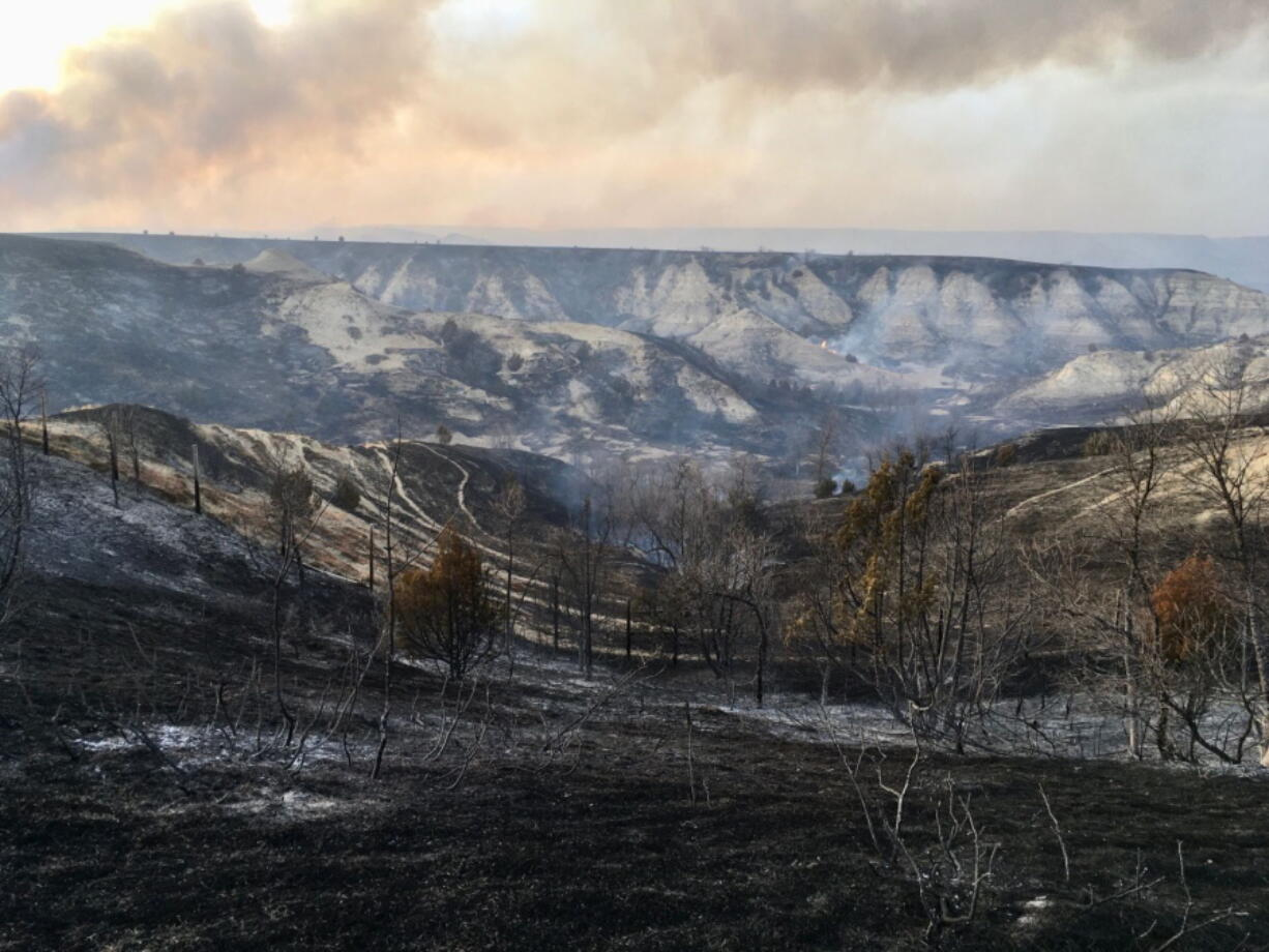 A wildfire smolders near the Burning Hills Amphitheatre Thursday, April 1, 2021 near Medora, N.D. Officials say firefighters have stopped a wildfire from spreading in the western North Dakota tourist town of Medora, where its 100 residents were forced to evacuate.
