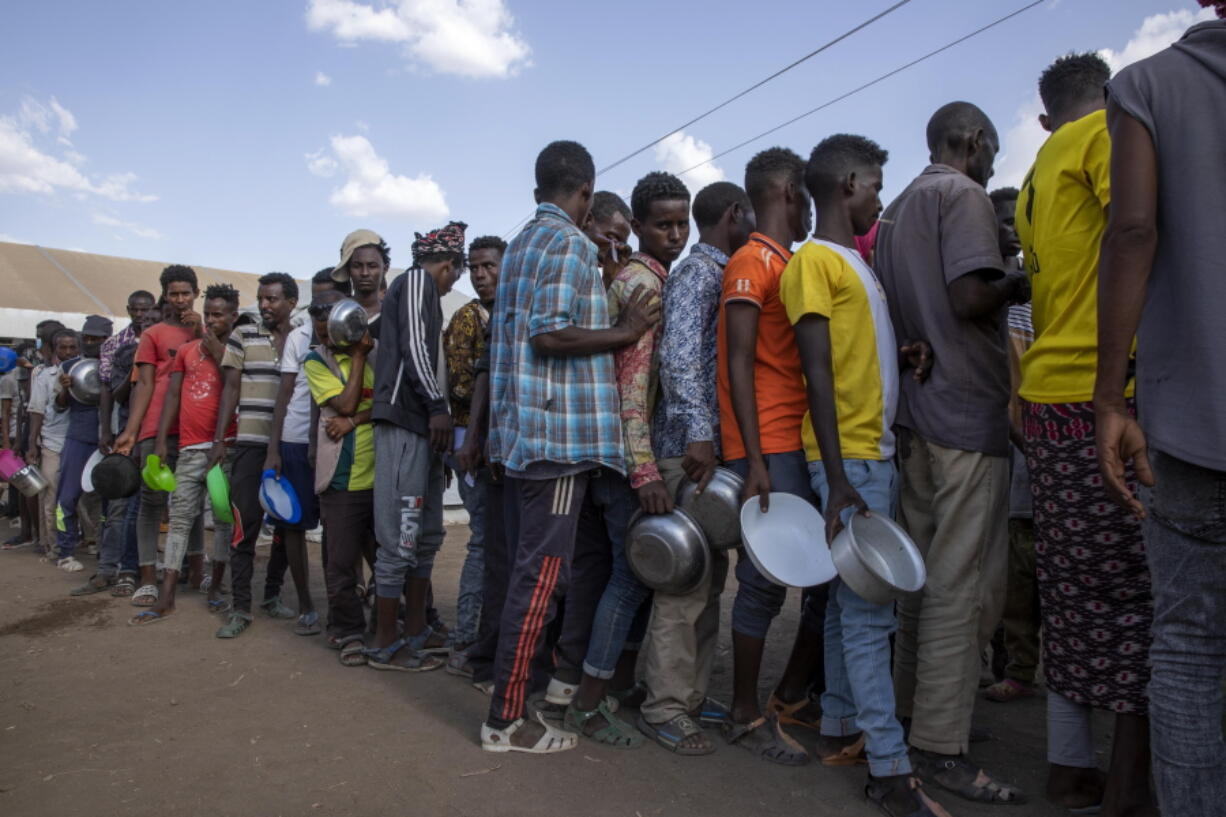 Tigrayan refugees wait in line to revive food from Muslim Aid at Hamdeyat Transition Center near the Sudan-Ethiopia border, eastern Sudan, Wednesday, March 24, 2021.