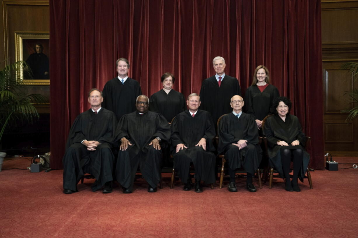 FILE - In this April 23, 2021, file photo members of the Supreme Court pose for a group photo at the Supreme Court in Washington. Seated from left are Associate Justice Samuel Alito, Associate Justice Clarence Thomas, Chief Justice John Roberts, Associate Justice Stephen Breyer and Associate Justice Sonia Sotomayor, Standing from left are Associate Justice Brett Kavanaugh, Associate Justice Elena Kagan, Associate Justice Neil Gorsuch and Associate Justice Amy Coney Barrett. Before the Supreme Court this is week is an argument over whether public schools can discipline students over something they say off-campus.