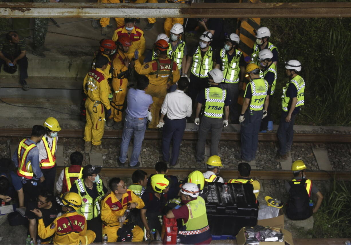 Rescue workers gather near the site of a derailed train near the Taroko Gorge area in Hualien, Taiwan on Friday, April 2, 2021. The train partially derailed in eastern Taiwan on Friday after colliding with an unmanned vehicle that had rolled down a hill, killing and injuring dozens.